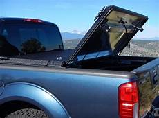 black truck bed cover on blue nissan frontier a black