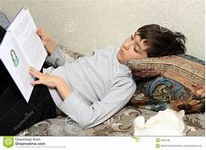 boy on bed with cat reading book royalty free stock image
