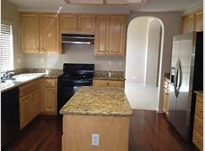 Kitchen with granite counters, stainless steel refrigerator, black appliance, and maple cabinets