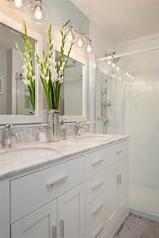 One Light Fixture Over Two Mirrors Small Bathroom With White Cabinets Under Two White Sinks