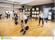 uomini sportivi uomini sportivi e donne che sollevano i bilancieri in