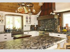 Cottage kitchen counters in Brazilian river rock granite called Black Maranaci. Kitchen has a