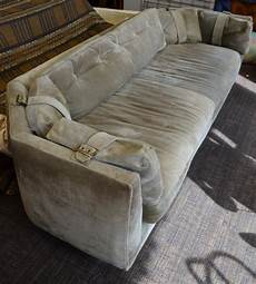 suede sofa of olive color with brass buckles