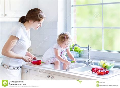 Washing Baby In Kitchen Sink And Cury Curly Toddler Washing Vegetables Stock