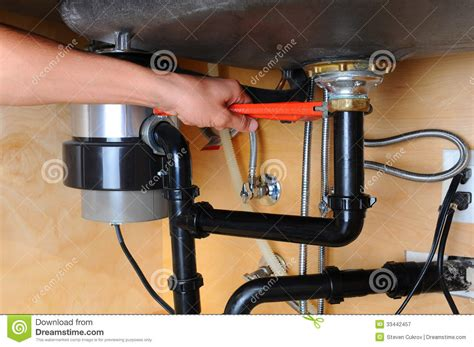plumbing kitchen sink plumber using wrench under kitchen sink royalty free stock