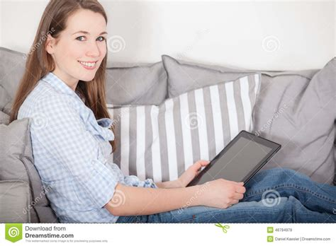sitting couch woman sitting on couch and uses tablet device stock image