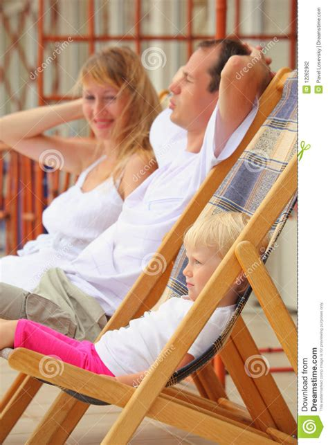 reclining girl happy family with girl reclining on chaise lounges stock