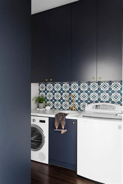 blue laundry room cabinets with oval brass knobs and slate floor tiles transitional laundry room