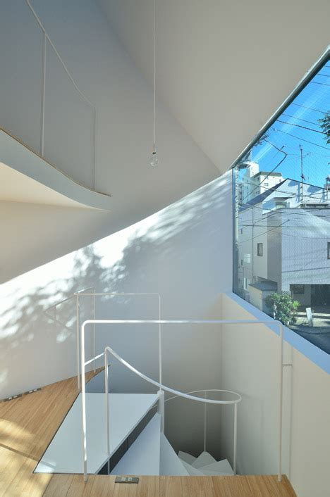 the bedroom window cast townhouse in takaban tokyo by niji architects contains two homes