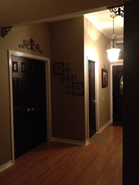 foyer black interior doors white trim walls scroll accent above door home decor