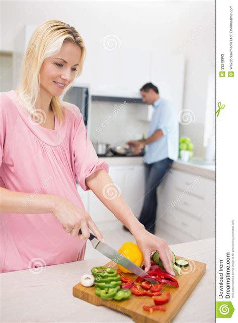 femme a la cuisine femme coupant des l 233 gumes avec l homme faisant la