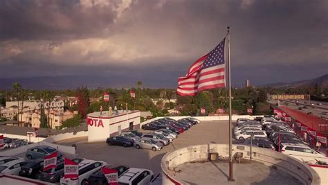 aerial view of dealership american flag on a background of winter mountains stock