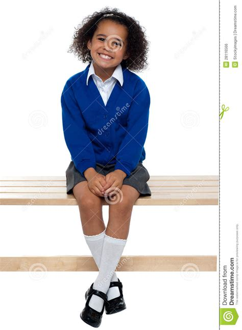 comfortably seated pretty school girl seated comfortably on a bench royalty