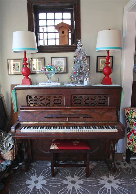 christmas decorations on top of the piano stately kitsch