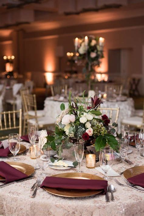 Reception table setting with lace linens, burgandy and