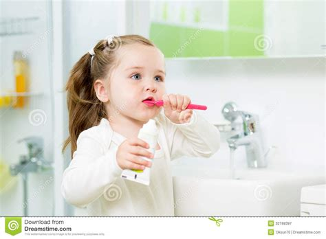 kid in bathroom child girl brushing teeth in bathroom stock image image
