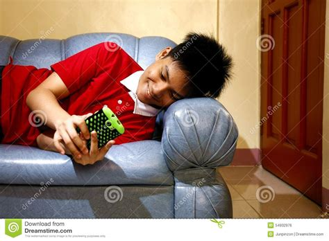 lying down on the couch teen using a smartphone while lying down on a couch and