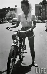 Singer eartha kitt riding her bicycle down the street in new york city