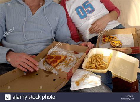 pizza sofa couple on a sofa eating pizza and chips fast food high in