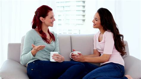 having on couch two cute women sitting on couch while chatting and holding