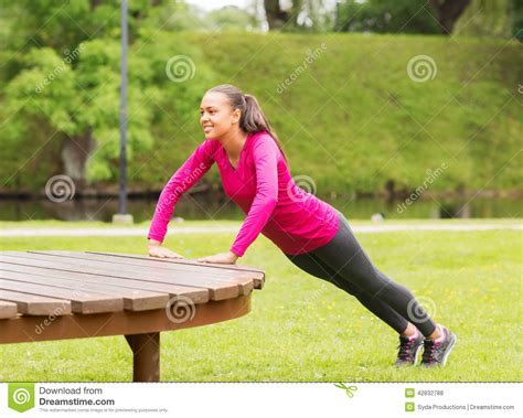 push ups on bench smiling woman doing push ups on bench outdoors stock photo image 42832788