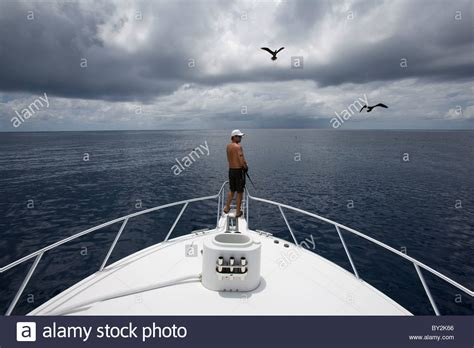 bow of a boat wide view of a man fishing off the bow of a boat with a