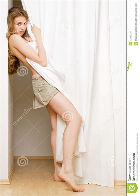 youngest looking women young woman looking from behind a white curtain stock