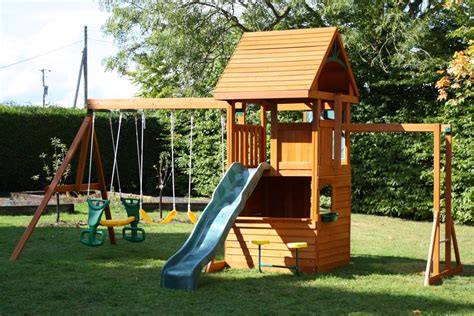 backyard playground design ideas light brown wooden building connected with blue slide also