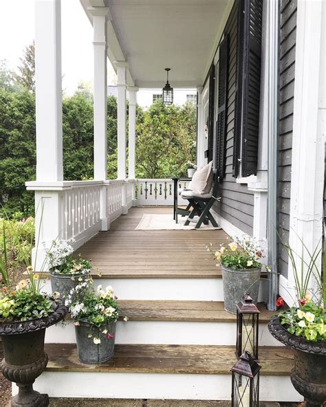 beautiful wood porch  white railings gray siding