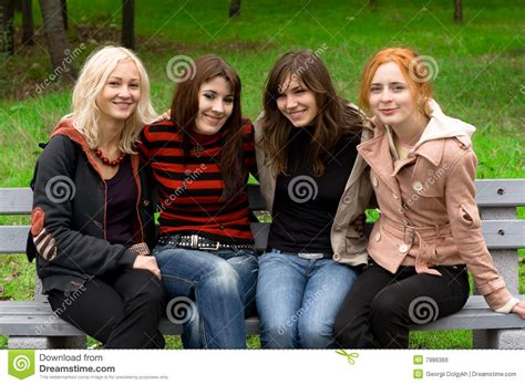 park bench group four girls sitting on a park bench stock photo image