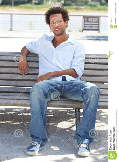 person sitting on a bench young man sitting on bench royalty free stock images