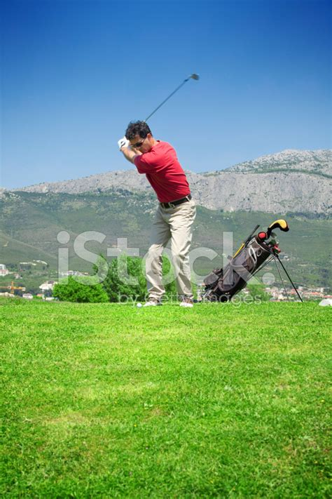 golf swing bag golfer taking a swing next too golf bag stock photos