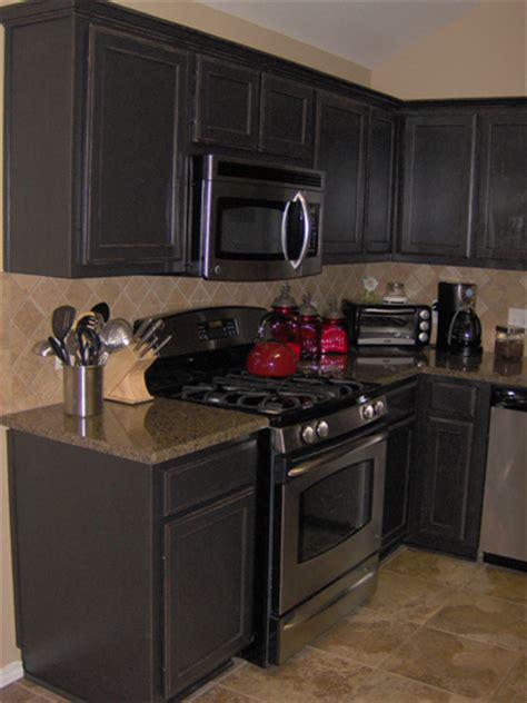 Kitchen cabinets painted a satin black then distressed and antiqued