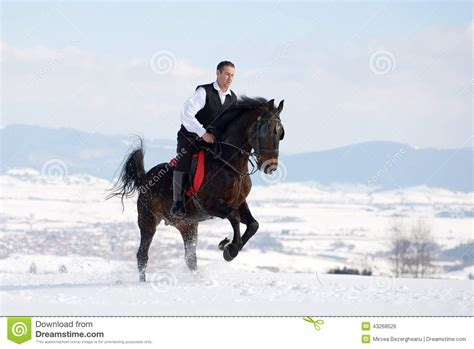 black riding young man riding horse outdoor in winter stock photo