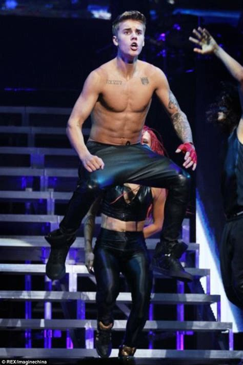 justin bieber whips his jacket off to bare chest