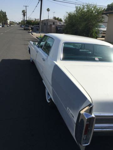 seller of classic cars 1965 cadillac deville (white/blue)