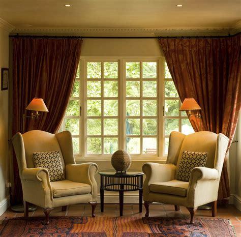 wall to wall curtain drapes framing a wall to wall window interior design