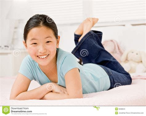 lay on the bed confident girl laying on bed in bedroom stock images