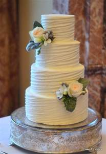 wedding cake buttercream simple 2 tier cake with rippled white icing and 2 decorative flowers 10 buttercream wedding