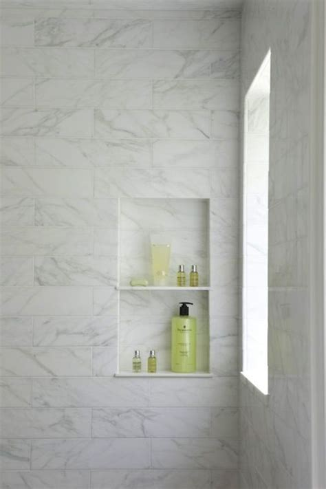 calcutta marble tiled shower with window and built in