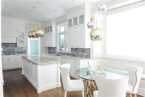 white kitchen with marble top island white glass kitchen white kitchen island with glass and mirror globe pendants