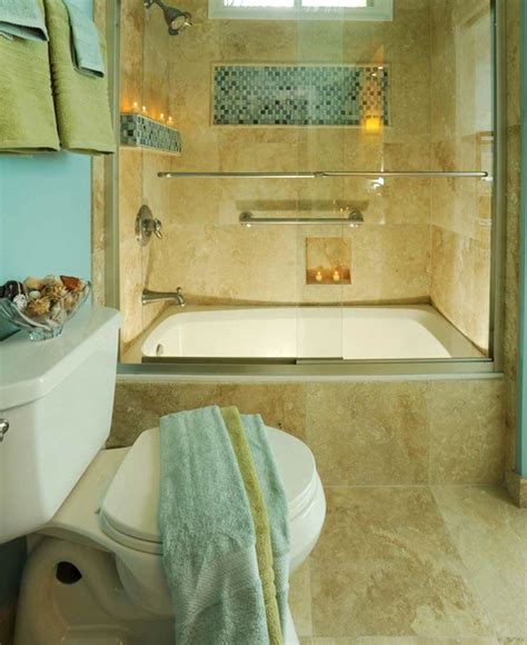 a travertine tile shower with glass mosaic accent is the highlight of this bathroom the paint