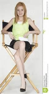 Teen red head girl modeling fashion in studio sitting down in director