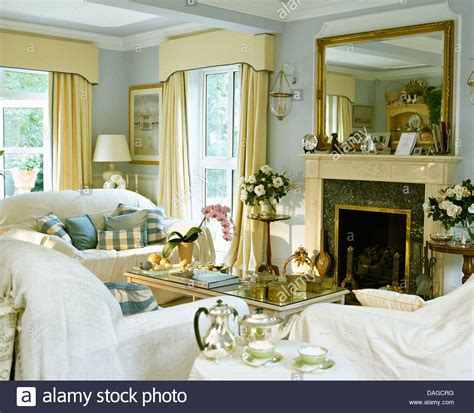 white throws on sofas in pale blue living room with large