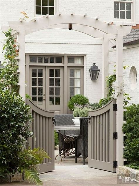 curved garden gate with arbor and hedge painted white brick house gardening