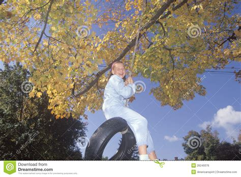 swinging new england a girl on a tire swing in autumn editorial photo image