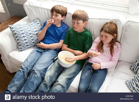 you sitting on the couch watching tv three kids are sitting on the couch watching tv and eating