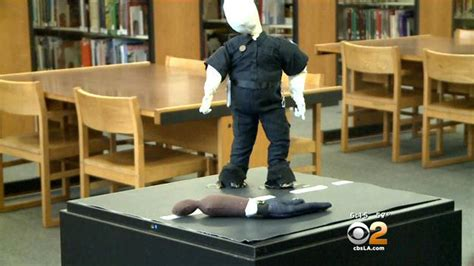black doll exhibit los angeles exhibit depicting white officer standing armless
