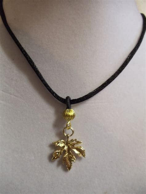 19 1 2 gold maple leaf pendant necklace on black by