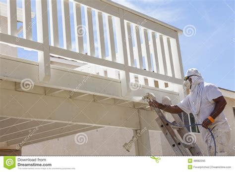 house spray painter house painter spray painting a deck of a home stock photo